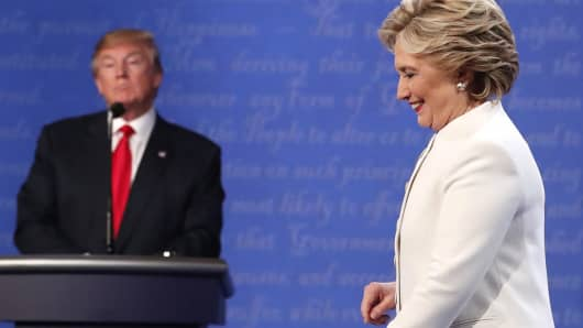 Hillary Clinton walks off the debate stage as Donald Trump remains at his podium after the conclusion of their debate.