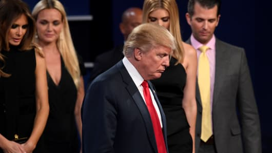 Republican presidential nominee Donald Trump (C) walks off the stage surrounded his wife Melania Trump (L), his son Donald Jr (R) and other memebers of his family after the final presidential debate at the Thomas & Mack Center on the campus of the University of Las Vegas in Las Vegas, Nevada on October 19, 2016.