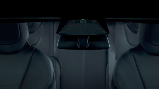 """Three cameras mounted behind the windshield provide broad visibility in front of the car, and focused, long-range detection of distant objects. There is a 120 degree fisheye lens for capturing traffic lights, obstacles, and objects at close range. Tesla says it is particularly useful in """"urban, low speed maneuvering."""" Tesla says it is particularly useful in """"urban, low speed maneuvering."""" The main camera has a broad range of use. A third narrow camera provides a focused, long-range view of distant features. Tesla says it is good for driving at high-speeds."""