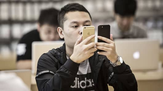 A customer inspects two Apple iPhone 7 smartphones at an Apple Store in Shanghai, China.