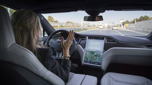 An employee drives a Tesla Motors Model S electric automobile equipped with Autopilot hardware and software hands-free on a highway in Amsterdam Netherlands