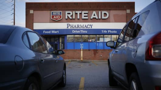 Vehicles sit parked outside of a Rite Aid Corp. store