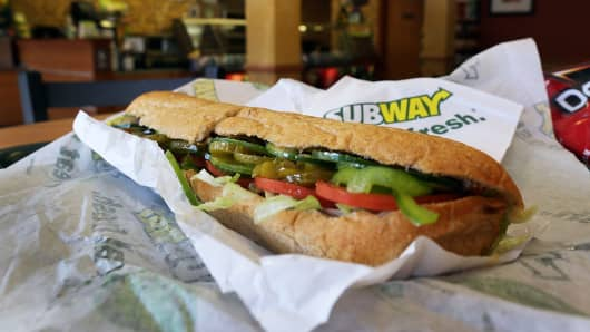 A Subway sandwich is seen in a restaurant.