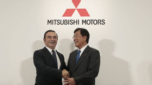 Carlos Ghosn, chairman and chief executive officer of Renault and Nissan Motor, left, shakes hands with Osamu Masuko, chairman and chief executive officer of Mitsubishi Motors, as they pose for a picture a during a news conference in Tokyo, Japan, on Thursday, Oct. 20, 2016.