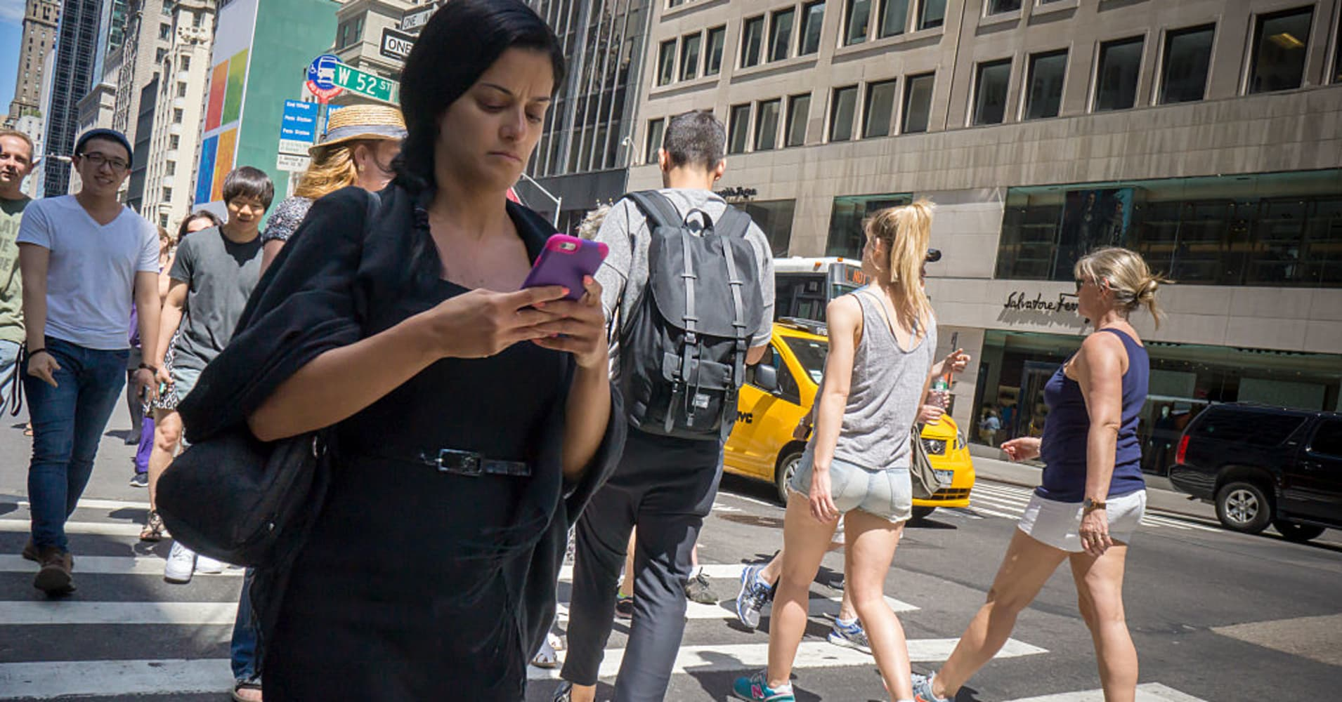 Woman walking, texting, NYC