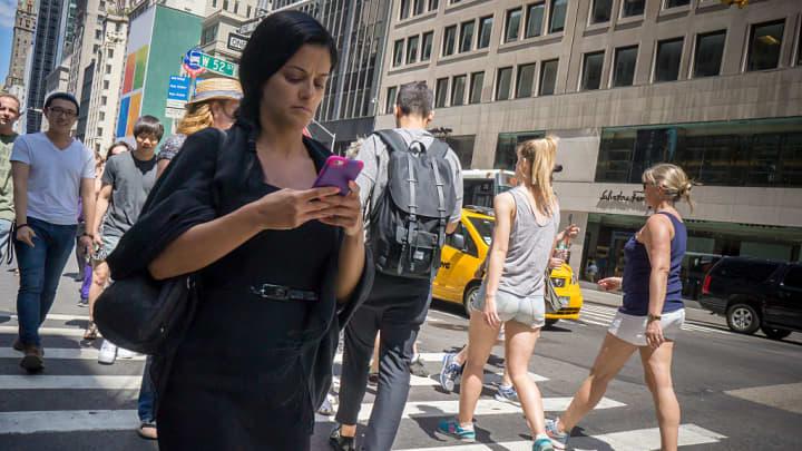 Woman walking, texting, NYC