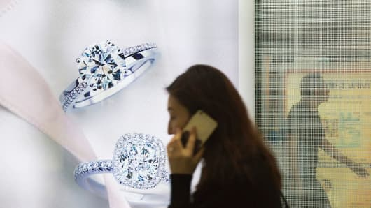 A pedestrian walks past a De Beers jewelry store.