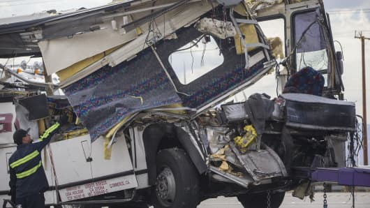 The front end of a charter tour bus is completely demolished after it crashed into the back of a big rig, killing 13 people.