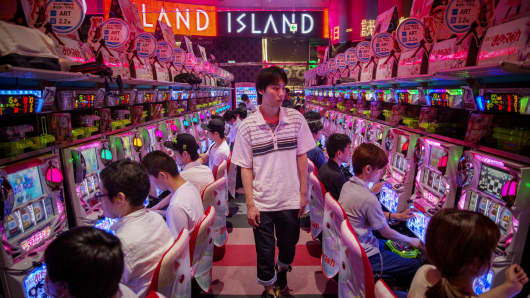 Customers play pachinko machines in a pachinko parlor in Tokyo.