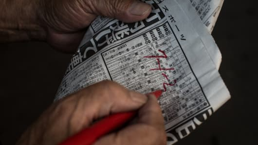 A punter writes down his picks on a form guide during the Keirin races at Kawasaki Velodrome on July 11, 2015 in Kawasaki, Japan. Keirin is a form of cycle racing developed in Japan around 1948 for gambling purposes and has since become extremely popular. It is one of only four sports that patrons are allowed to bet on.