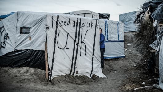 A refugee outside his tent where it is written: I need to go to England, in Calais, France.