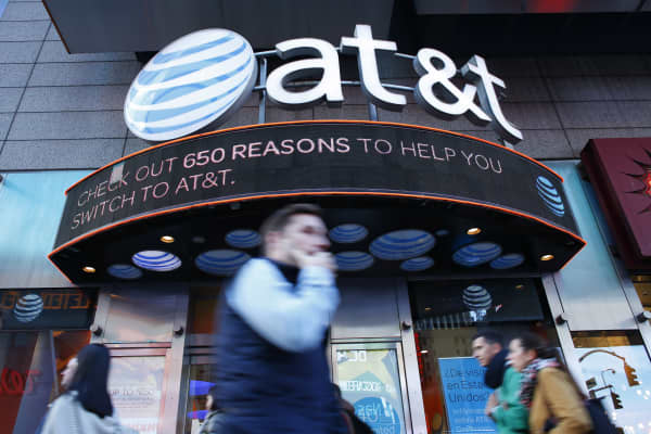 People walk past an AT&T store in New York.