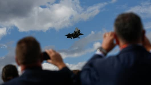 Attendees take photographs of the Lockheed Martin Corp. F-35