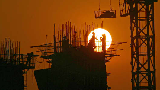 Chinese laborers work at a construction site at sunset in Chongqing, China.