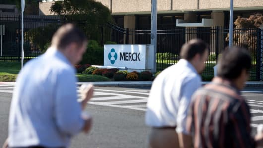 Pedestrians walk across the street from a Merck & Co. facility in Summit, New Jersey