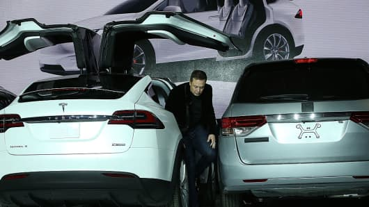Tesla CEO Elon Musk steps out of the new Tesla Model X during an event to launch the company's new crossover SUV on September 29, 2015 in Fremont, California.