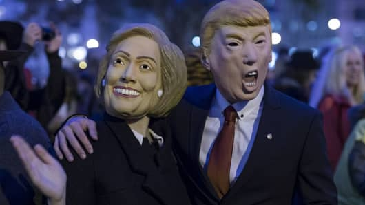 People wearing the masks of presidential candidates Hillary Clinton and Donald Trump are seen during the 42nd Annual Halloween Parade on October 31, 2015 in New York City.