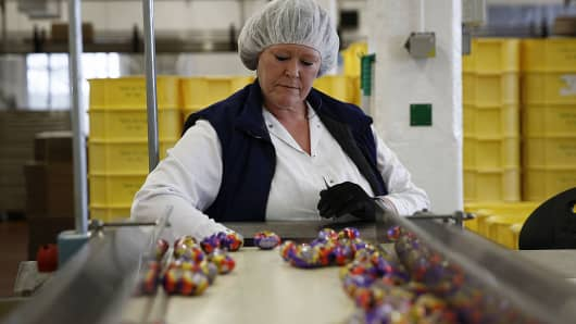 An employee monitors foil-wrapped Cadbury Creme Eggs as they move along the production line at the Bournville Cadbury factory, operated by Mondelez International Inc., in Birmingham, U.K.