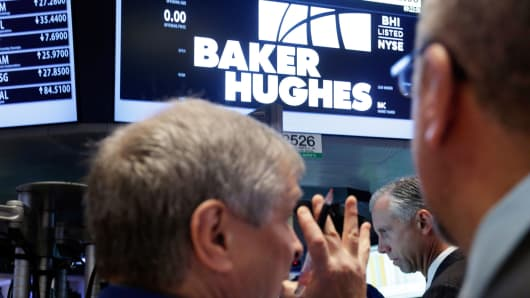 Traders gather at the post that handles Baker Hughes on the floor of the New York Stock Exchange.