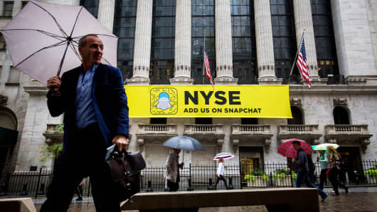 Pedestrians hold umbrellas while walking past a Snapchat sign displayed outside of the New York Stock Exchange in New York, Oct. 21, 2016.