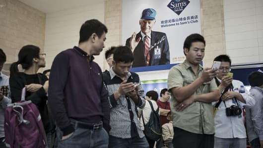 Customers look at mobile handsets as an advertisement featuring a photo of Wal-Mart Stores Inc.. founder Sam Walton hangs on a wall in a Wal-Mart Stores Inc. owned and operated Sam's Club store during its opening day in Tianjin, China, on Wednesday, Sept. 28, 2016.