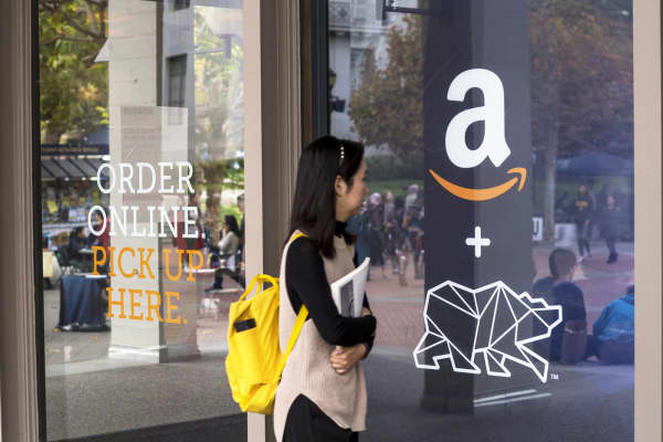 A student walks in front of an Amazon.com Inc. kiosk on the University of California, Berkeley campus in Berkeley, California.