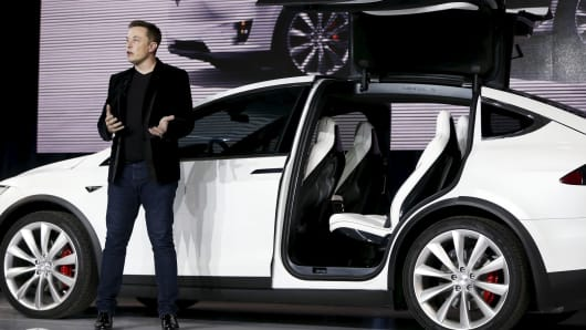 "Tesla Motors CEO Elon Musk introduces the ""falcon wing"" door on the Model X electric sports-utility vehicle during a presentation in Fremont, California, on September 29, 2015."