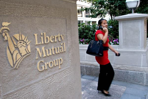 A woman walks out of the headquarters of Liberty Mutual Insurance Co. in Boston.
