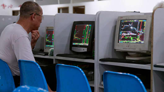 An investor looks at Stock index quotes at a brokerage firm in Shanghai.