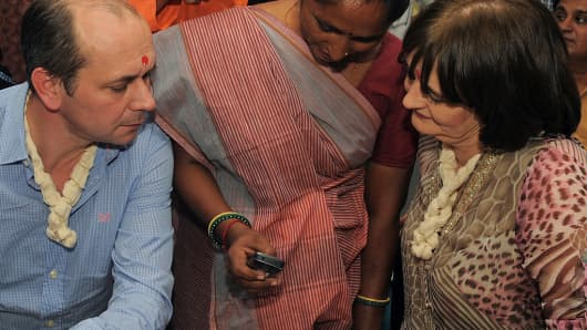 Cherie Blair (R), wife of former British prime minister Tony Blair and chairperson of the Cherie Blair Foundation for Women, and Vodafone Foundation's global director Andrew Dunnett are briefed on a mobile application during their visit to an agricultural processing centre in India