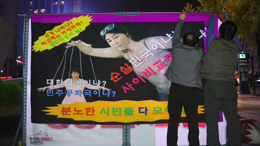 Protesters hang a caricature showing President Park Geun-Hye (L) and her confidante Choi Soon-Sil (C) during a rally in Seoul on October 27, 2016.