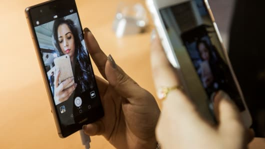 An attendee uses her smartphone to take a picture of her selfie on the camera app of a P9 smartphone launched by Huawei in India.