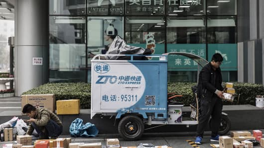 People sort through packages next to a ZTO Express delivery vehicle outside an office building in Beijing, China>