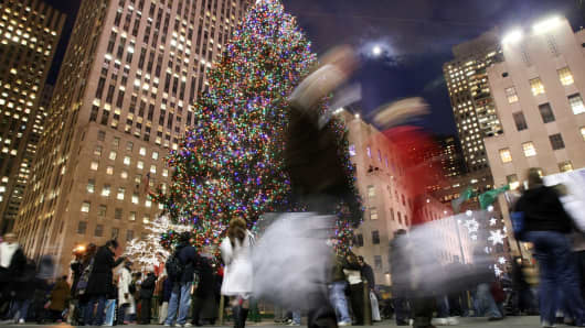 Shoppers walk past the Rockefeller Center Christmas tree in New York.