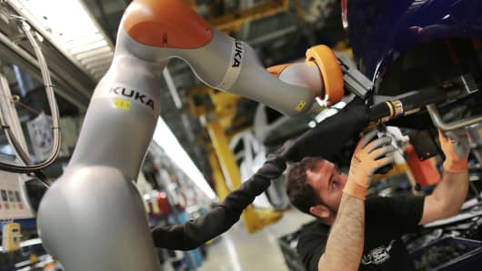 A Ford employee assembling a buffer using a Kuka co-bot in Cologne, Germany.