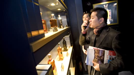 A visitor looks at Johnnie Walker bottles at the luxury goods fair in Shanghai China.