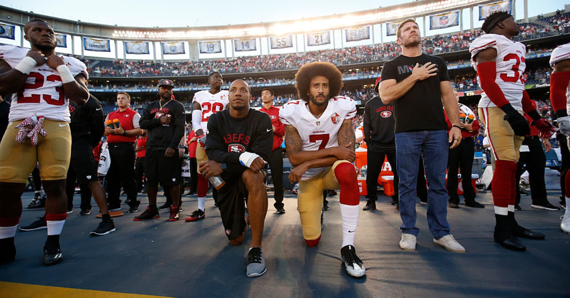 Eric Reid #35 and Colin Kaepernick #7 of the San Francisco 49ers kneel on the sideline during the anthem