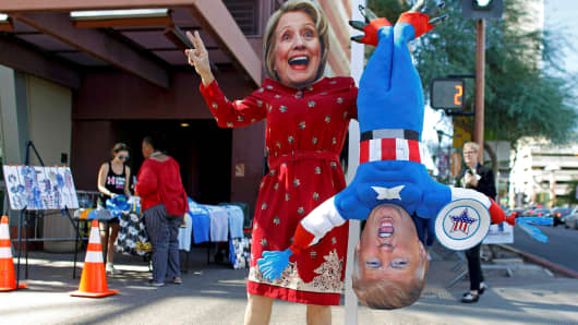 A man wears a mask depicting Democratic U.S. presidential candidate Hillary Clinton while holding a doll depicting Republican presidential nominee Donald Trump in Phoenix, Arizona October 20, 2016.