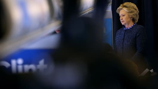 Democratic presidential nominee former Secretary of State Hillary Clinton talks with members of her staff aboard her campaign plane at Westchester County Airport on October 28, 2016 in White Plains, New York.