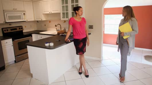 A real estate agent shows a home for sale to a prospective buyer in Miami.