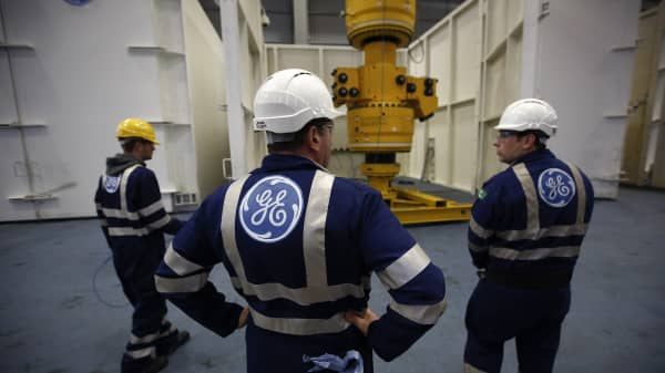 Employees stand as a subsea oil and gas tree is maneuvered by a crane at the General Electric Co. (GE) manufacturing plant in Montrose, U.K.