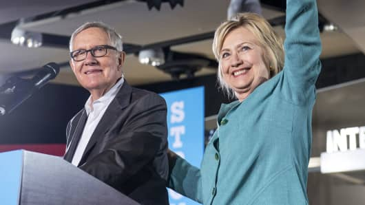 Hillary Clinton, 2016 Democratic presidential nominee, right, waves on stage with Senate Minority Leader Harry Reid, a Democrat from Nevada, during a campaign event in Las Vegas, Aug. 4, 2016.