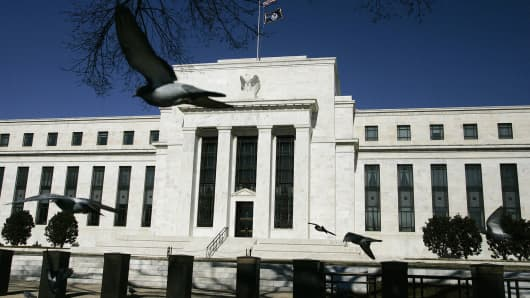 Pigeons fly past the US Federal Reserve in Washington.
