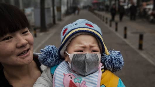 A Chinese girl wears a mask as she is held by her mother outside a local hospital in Beijing, China, during a day of heavy smog on December 8, 2015.
