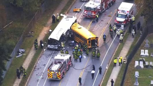 In this frame from video, emergency personnel work at the scene of a fatal school bus and a commuter bus crash in Baltimore, Tuesday, Nov. 1, 2016.