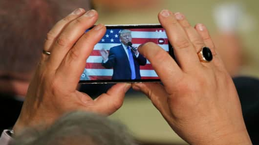A man uses cell phone to take a photo of Republican presidential candidate Donald Trump as he speaks at a town hall event in Sandown, New Hampshire.