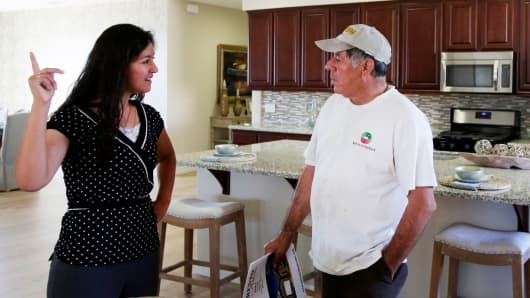 A sales manager gives a tour of a model home to a prospective buyer in Hesperia, California.