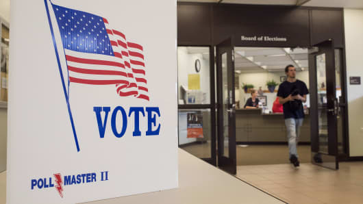 A voting sign sits on a table as an early voter walks out of the Fairfield County Board of Elections Office in Lancaster, Ohio, on Saturday, Oct. 29, 2016.