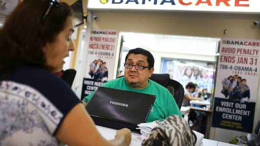 Shopping for an insurance plan available through the Affordable Care Act at a store setup in Miami, Florida.