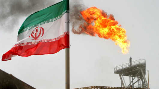 A gas flare on an oil production platform in the Soroush oil fields is seen alongside an Iranian flag in the Gulf.